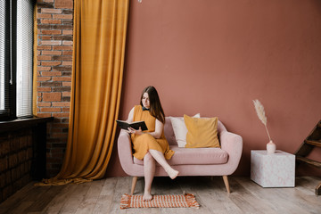 Overweight lady reading book on couch