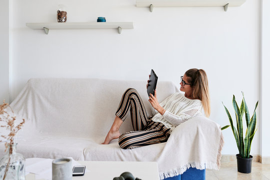 Video call with tablet device sitting sofa.