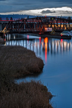 Rail Bridge and Highway with Light Trails over Grassy Waterway