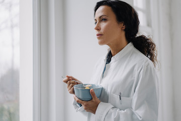 Female doctor eating a snack, standing at window