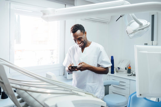 Happy dentist using cell phone in his medical practice