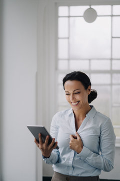 Successful businesswoman, standing by window, using digital tablet, smiling