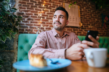 Portrait of a man in a cafe holding cell phone