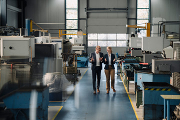 Businessman and businesswoman walking and talking in a factory