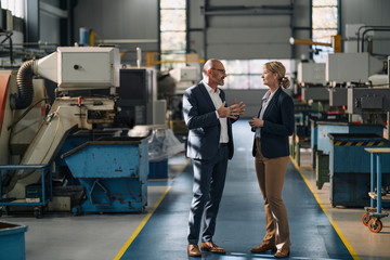 Businessman and businesswoman talking in a factory
