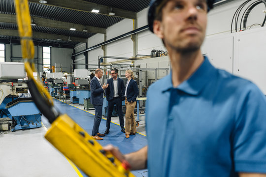 Business people having a meeting in a factory with worker operating machine in foreground