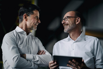 Two smiling men with tablet talking in a factory