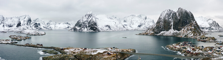 Norway, Reine, Aerial panorama of fishing village on shore of Moskenesoya island with mountains in background Wall mural