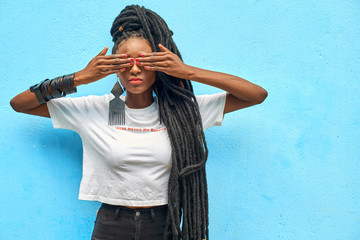 Portrait of woman with long dreadlocks covering her eyes in front of turquoise wall