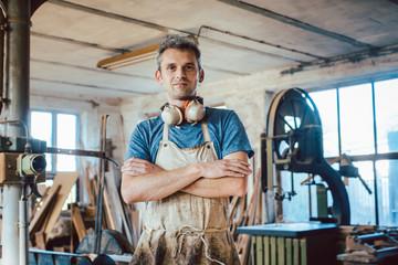 Fototapeta Carpenter standing in his wood workshop looking at camera obraz