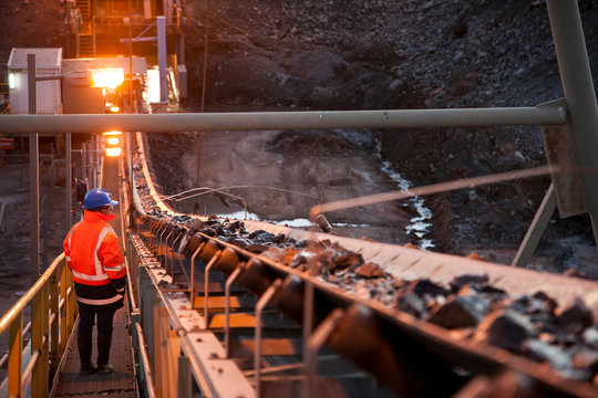 Nyngan Australia June 20th 2012 : Shallow depth of field image of a miner inspecting ore rocks on a conveyor in NSW Australia