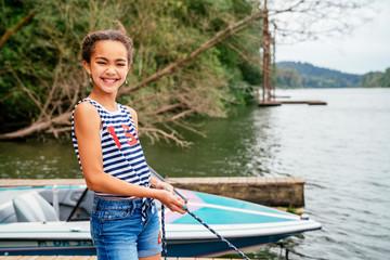 Smiling, girl pulling in boat on dock on lake