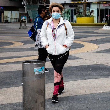 young woman walking on the street with a mask covering her face to protect from the coronavirus