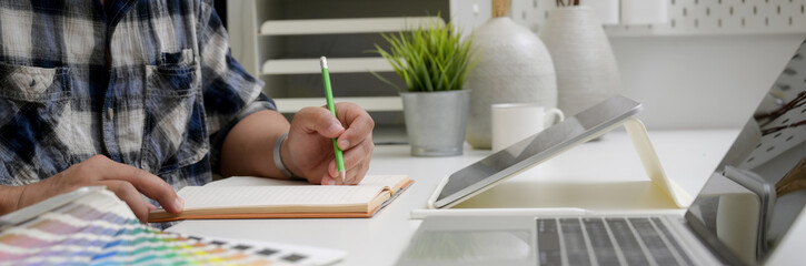 Side view of male graphic designer working on sketch paper, tablet and laptop on office desk Fototapete