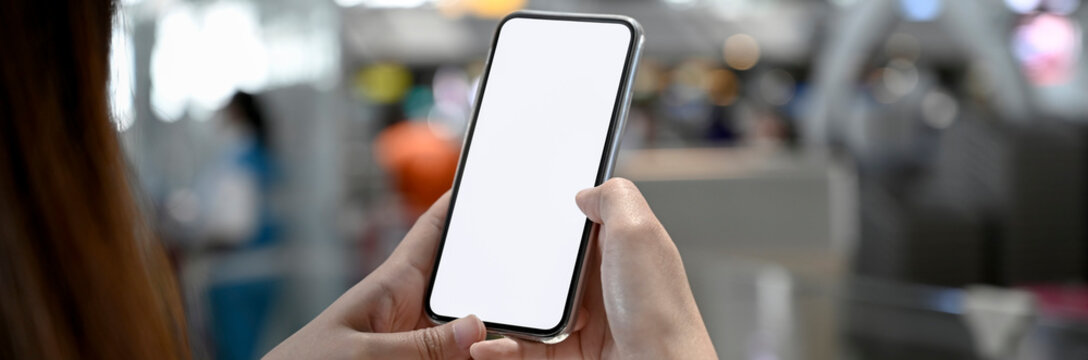 Cropped shot of a woman using blank screen smartphone in blurred airport backgroud