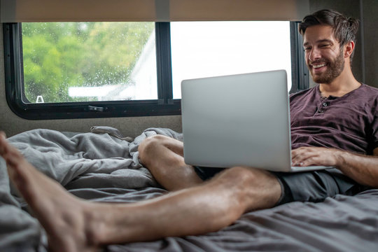A bearded brown haired hypster man wearing a red t-shirt lays down relaxing on his bed in his camper typing and communicating to someone on his cmoputer on a cloudy rainy afternoon in an rv park