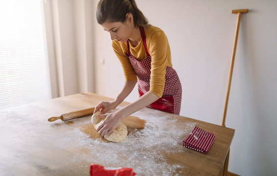 Young woman kneading dough for baking homemade bread