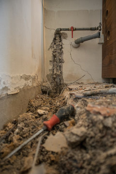 Broken water pipe in an apartment. Visible hole in the ground with tiles, old concrete and debris. Construction site while trying to remedy a water leak at home with pipe and closed valve on the wall