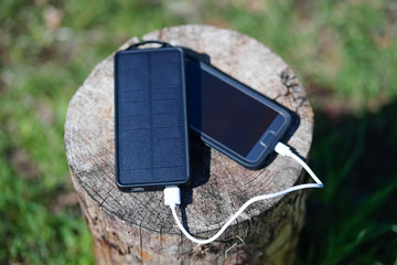 Solar USB charger, charging smartphone on wilderness camping trip
