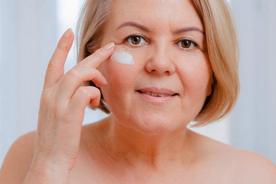 Smiling senior woman applying anti-aging lotion to remove dark circles under eyes.