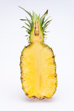 pineapple cut in half isolated in front of a white background. The yellow core of the fruit is juicy and colorfull with green leaves