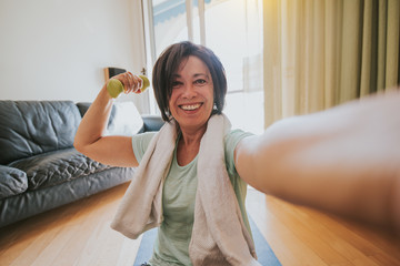 Happy mature woman taking a selfie at workout gym at home during quarantine. Concept about people, gym at home, sport.