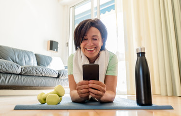 Beautiful brunette older woman training gym at home holding smartphone. Senior female workout with fitness app on the phone. Concept about people, sport, quarantine.