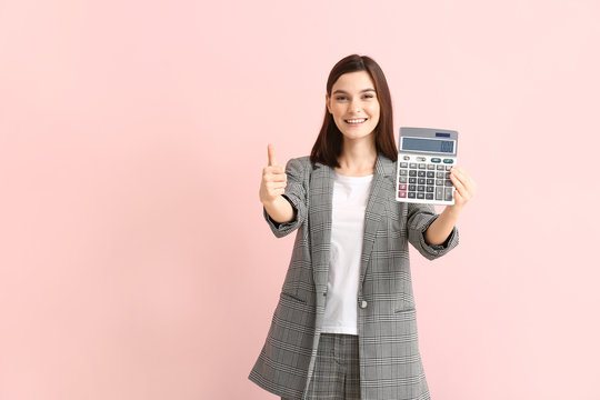Young woman with calculator showing thumb-up on color background