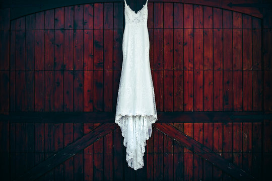 A white wedding dress hanging against a mahogany colored wooden door