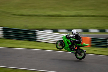 A panning image of a green racing bike passing and leaving the ground altogether. Wall mural