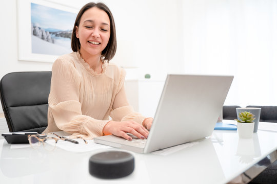 Cheerful happy woman talking to voice assistant