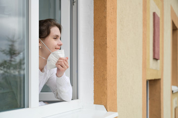 Caucasian young woman smiles, looks out of the apartment window and takes off her protective mask. End of quarantine, self-isolation and the COVID-19 pandemic. Horizontal orientation, copy space.