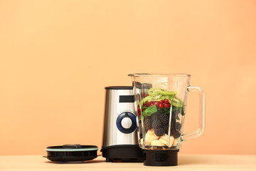 Blender with ingredients for healthy smoothie on color background