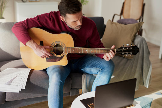 Man having a home course of guitar play