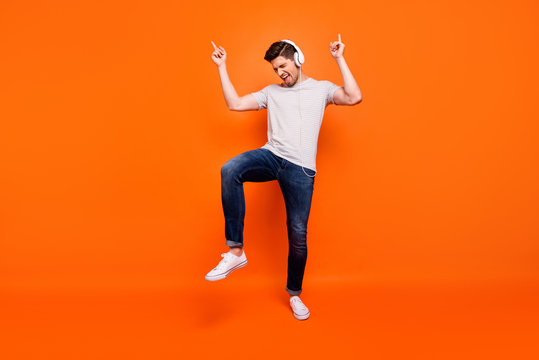Full body photo of funky cool guy cheerful party mood chilling listening earphones direct fingers up empty space wear striped t-shirt jeans shoes isolated bright orange color background