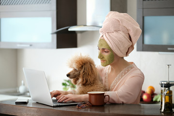 Woman applying facial clay mask. The young woman is working remotely. Concept of the workplace at home, working remotely. Creative.