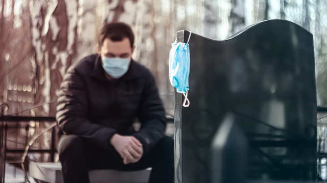 A man in a medical mask grieves sitting at the tombstone. Death from a coronavirus. A relative of the deceased person in the cemetery. A medical mask weighs on a tombstone.