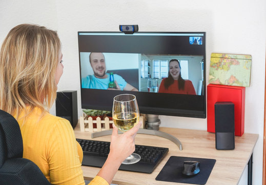 Young woman chatting maging video call with friends while drinking wine and laughing together - Alternative party during home isolation quarantine - Focus on glass hand