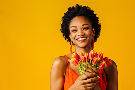 Portrait of a happy smiling young woman with orange tulips bouquet
