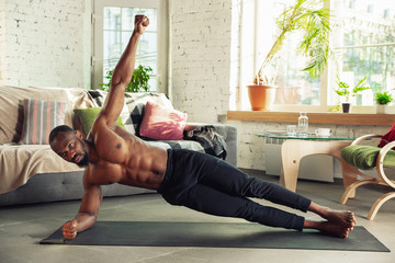African-american man teaching at home online courses of fitness, aerobic, sporty lifestyle while being quarantine. Getting active while isolated, wellness, movement concept. Training, plank.