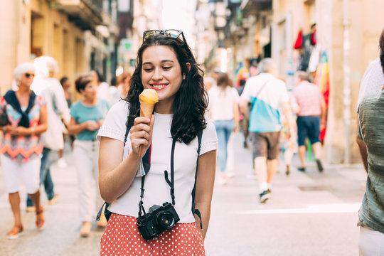 Young tourist woman enjoying an ice cream while exploring the city