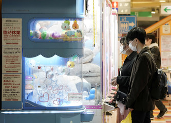 People wearing protective masks play claw machine, following the coronavirus disease (COVID-19) outbreak, in Tokyo