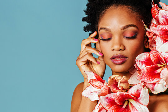 Portrait of a beautiful young woman with pink make up, lips, nail polish and amaryllis flower blooms around face and eyes closed