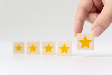 Hand putting wooden cube with five star shape on white background. The best excellent business services rating customer experience concept