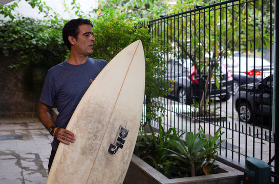 Surfer Bruno Bocayuva holds his surfboard at his apartment complex, amid the coronavirus disease (COVID-19) outbreak, in Rio de Janeiro