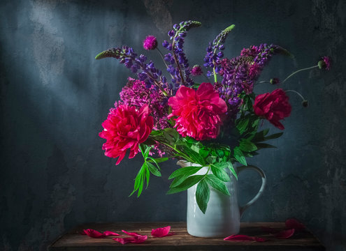 Classic still life with beautiful purple peony and lupin flowers bouquet in white jug. Art photography.