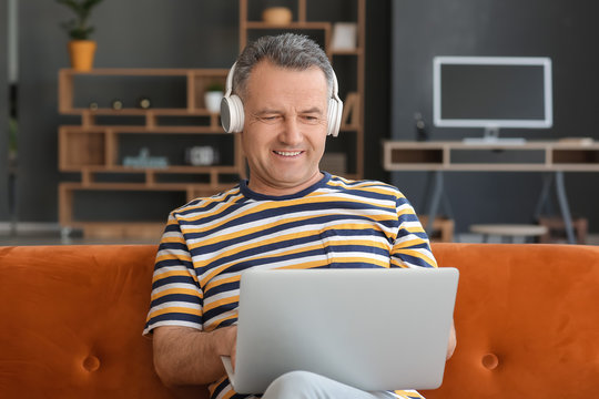 Mature man with laptop and headphones sitting on sofa at home