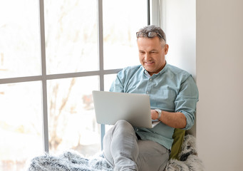 Mature man using laptop at home Fotomurales