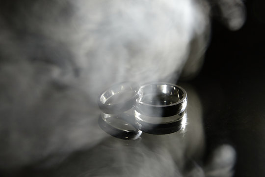 Two golden wedding rings with smoke on mirror background, copy space. Wedding card, Valentines Day