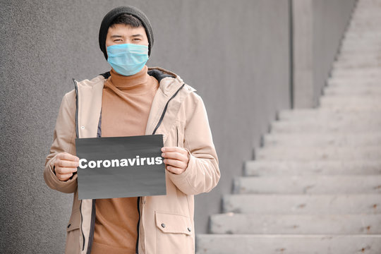 Asian man wearing protective mask on city street. Concept of Coronavirus epidemic